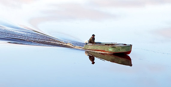 Man boating in still water